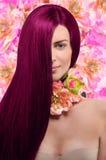 Portrait d'une fille avec des cheveux de Bourgogne sur le fond floral Photos libres de droits