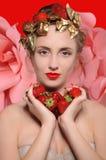 Portrait d'une fille avec des fraises dans des mains et sur sa tête dessus Photographie stock libre de droits