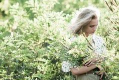 Portrait d'une fille avec du charme dans une herbe grande au coucher du soleil, Photographie stock
