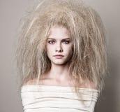 Portrait d'une fille avec la coiffure pelucheuse élevée dans des rococos baroques de style et le maquillage lumineux dans un beig Image stock