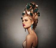 Portrait d'une fille avec la coiffure pelucheuse élevée dans des rococos baroques de style et le maquillage lumineux dans un beig Photographie stock