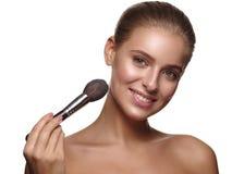 Portrait d'une fille avec la peau lisse rougeoyante pure et saine, qui applique le maquillage quotidien sur son visage utilisant  image stock
