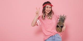 Portrait d'une fille avec un ananas sur un fond rose photographie stock
