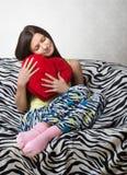 Portrait d'une fille avec un coussin rouge de coeur photographie stock
