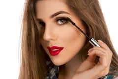 Portrait d'une fille avec une brosse de maquillage pour la mèche dans des mains Photo stock