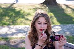 Portrait d'une fille blonde qui met le maquillage sur les l?vres rouges et utilise son t?l?phone comme miroir photo stock