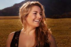 Portrait d'une fille blonde riante avec les cheveux d'or Photos stock