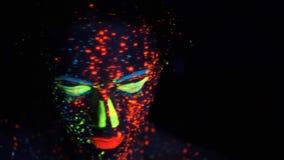 Portrait d'une fille dans la lampe au n?on visage peint avec la lueur dans la peinture fonc?e banque de vidéos