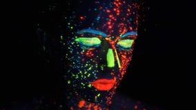 Portrait d'une fille dans la lampe au n?on visage peint avec la lueur dans la peinture fonc?e clips vidéos