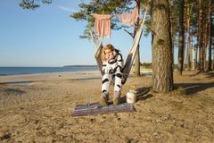 Portrait d'une fille dans un costume de vache dormant sur une plage Photographie stock