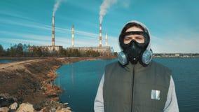 Portrait d'une fille dans un masque de respirateur ou de gaz À l'arrière-plan la fumée vient des tuyaux d'une énergie hydroé clips vidéos