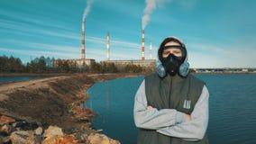 Portrait d'une fille dans un masque de respirateur ou de gaz À l'arrière-plan la fumée vient des tuyaux d'une énergie hydroé banque de vidéos