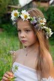 Portrait d'une fille dans une guirlande des camomilles sur sa tête avec une fleur dans les mains Photos libres de droits