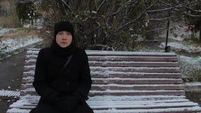 Portrait d'une fille dans une robe noire, se reposant sur un banc en parc en hiver banque de vidéos