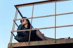 Portrait d'une fille de brune, dans des vêtements foncés se reposant sur le balc Photo stock