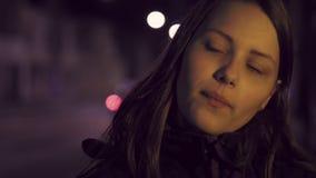 Portrait d'une fille de l'adolescence de sourire songeuse mignonne sur une rue de ville de nuit slowmo de 4K UHD banque de vidéos