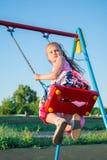 Portrait d'une fille de sept ans dans une robe rose lumineuse balançant sur une oscillation en parc contre un ciel bleu dans Photos stock