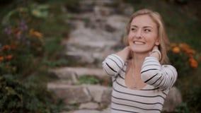 Portrait d'une fille de sourire s'asseyant sur les escaliers dans le jardin banque de vidéos