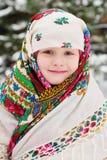 Portrait d'une fille d'enfant dans un foulard dans le style d'Urs sur le fond de la neige et de la forêt photographie stock libre de droits