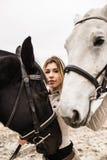 Portrait d'une fille entre deux chevaux Photographie stock libre de droits