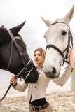 Portrait d'une fille entre deux chevaux Photos stock