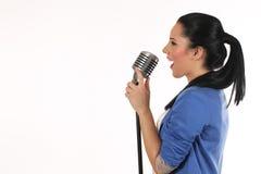 Portrait d'une fille fascinante tenant un microphone et un chant photo libre de droits