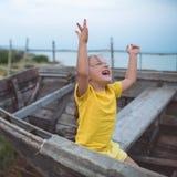 Portrait d'une fille joyeuse s'asseyant dans un vieux bateau une soirée d'été photographie stock
