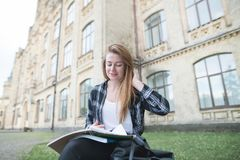 Portrait d'une fille positive dans une chemise se reposant sur un banc près d'un bâtiment d'université, lisant un livre et un sou photographie stock