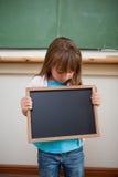 Portrait d'une fille regardant une ardoise d'école Image libre de droits