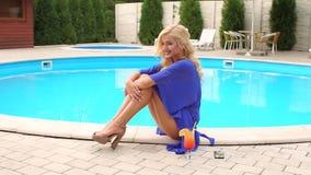 Portrait d'une fille sexy s'asseyant près de la piscine banque de vidéos