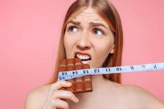 Portrait d'une fille songeuse mordant une barre de chocolat enveloppée avec un ruban métrique sur un fond rose photographie stock