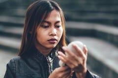 Portrait d'une fille sur la rue regardant le miroir de maquillage Photo libre de droits