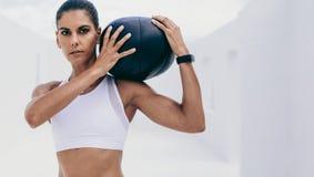 Portrait d'une formation d'athlète de femme avec un medicine-ball photographie stock