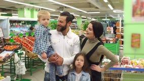 Portrait d'une grande famille heureuse avec deux enfants dans le supermarché banque de vidéos