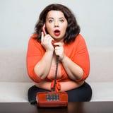 Portrait d'une grosse femme adulte étonnée avec un téléphone Photographie stock