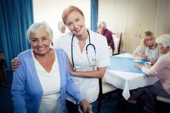Portrait d'une infirmière aidant un aîné employant un marcheur Photographie stock libre de droits