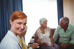 Portrait d'une infirmière de sourire avec des aînés Images stock