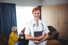 Portrait d'une infirmière de sourire avec l'aîné Photos libres de droits