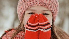 Portrait d'une jeune écolière avec des taches de rousseur dans les bois en hiver Il chauffe ses mains dans des mitaines et les ap photo libre de droits