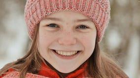 Portrait d'une jeune écolière avec des taches de rousseur dans les bois en hiver La fille touche son nez avec sa main dans photos stock