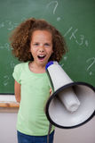 Portrait d'une jeune écolière criant par un mégaphone Photo libre de droits