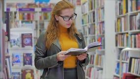 Portrait d'une jeune belle femme aux cheveux rouges vifs dans les lunettes, jolie lecture de livres Université de la Bibliothèque banque de vidéos