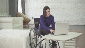 Portrait d'une jeune belle femme handicapée de sourire dans un fauteuil roulant, travaillant à la maison sur un ordinateur portab banque de vidéos