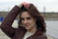 Portrait d'une jeune belle fille avec de longs cheveux bruns Un jour nuageux d'automne sur la plage Photo libre de droits
