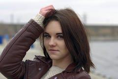 Portrait d'une jeune belle fille avec de longs cheveux bruns Un jour nuageux d'automne sur la plage Photo stock