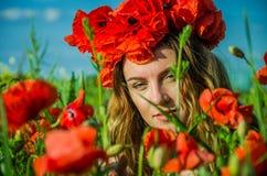 Portrait d'une jeune belle fille dans un domaine de pavot avec une guirlande des pavots sur sa tête un jour ensoleillé d'été chau Image libre de droits