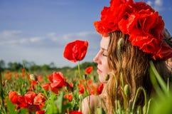 Portrait d'une jeune belle fille dans un domaine de pavot avec une guirlande des pavots sur sa tête un jour ensoleillé d'été chau Image stock