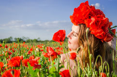 Portrait d'une jeune belle fille dans un domaine de pavot avec une guirlande des pavots sur sa tête un jour ensoleillé d'été chau Photographie stock libre de droits