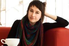 Portrait d'une jeune belle fille dans une écharpe rayée tricotée image stock