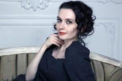 Portrait d'une jeune dame avec du charme détendant sur le divan Photo libre de droits